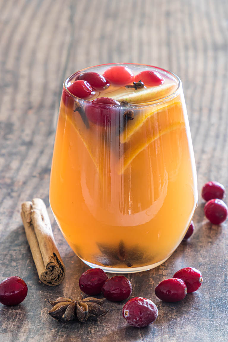 one glass of instant pot apple cider garnished with cranberries