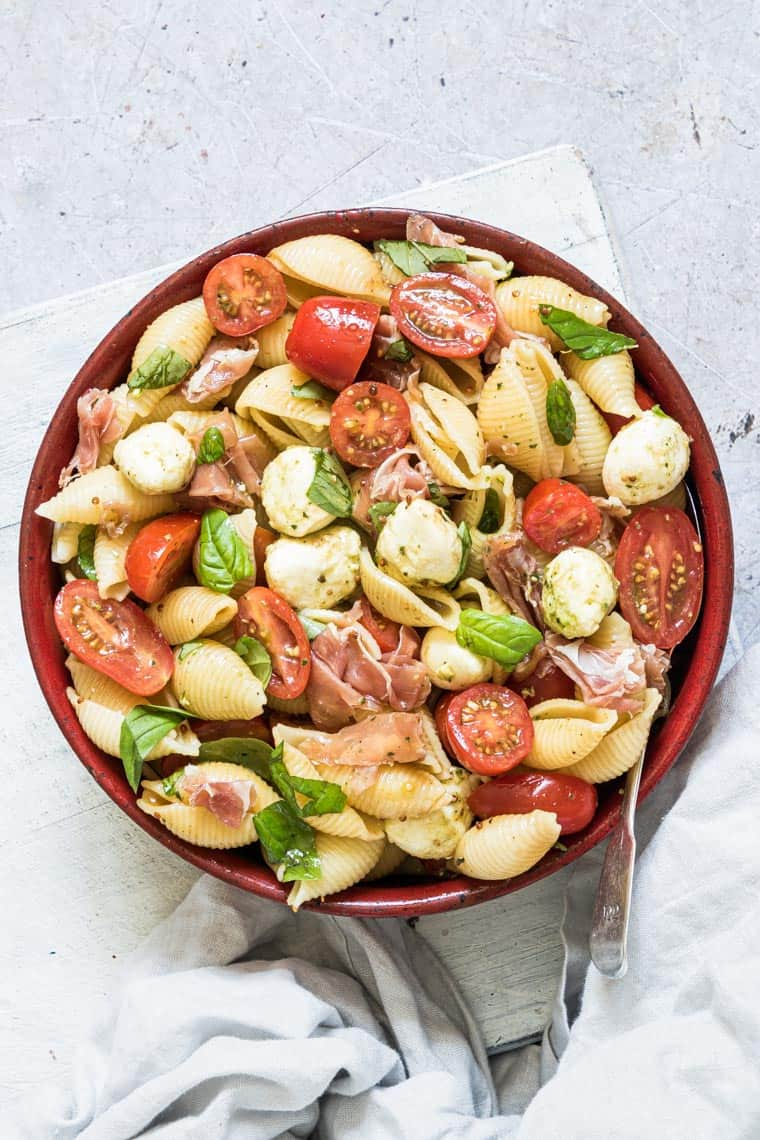 caprese pasta salad with parma ham served in a red bowl