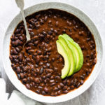 a bowl of instant pot black beans stew served with sliced avocado