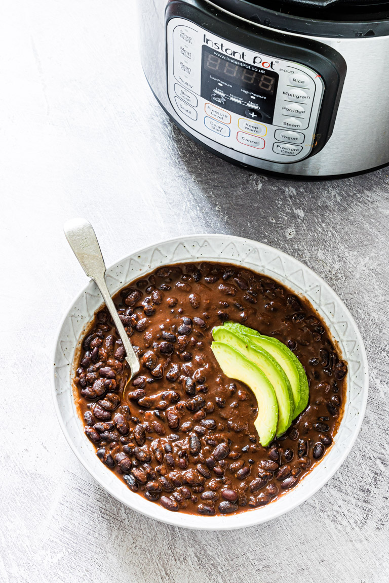 a serving of instant pot black beans stew garnished with sliced avocado set in front of the instant pot