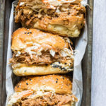 three instant pot pulled chicken sandwiches served in a tray