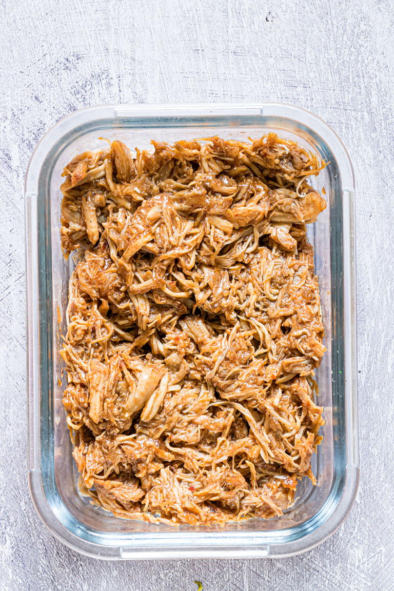 instant pot pulled chicken inside a glass meal prep container