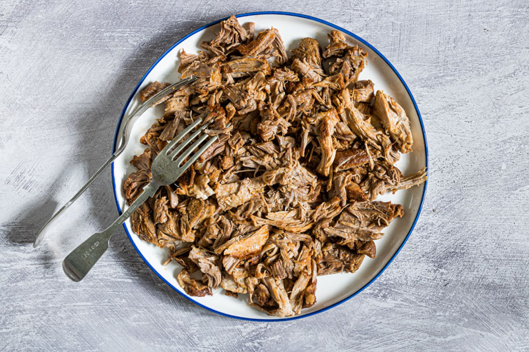a plate of instant pot pulled pork with two forks