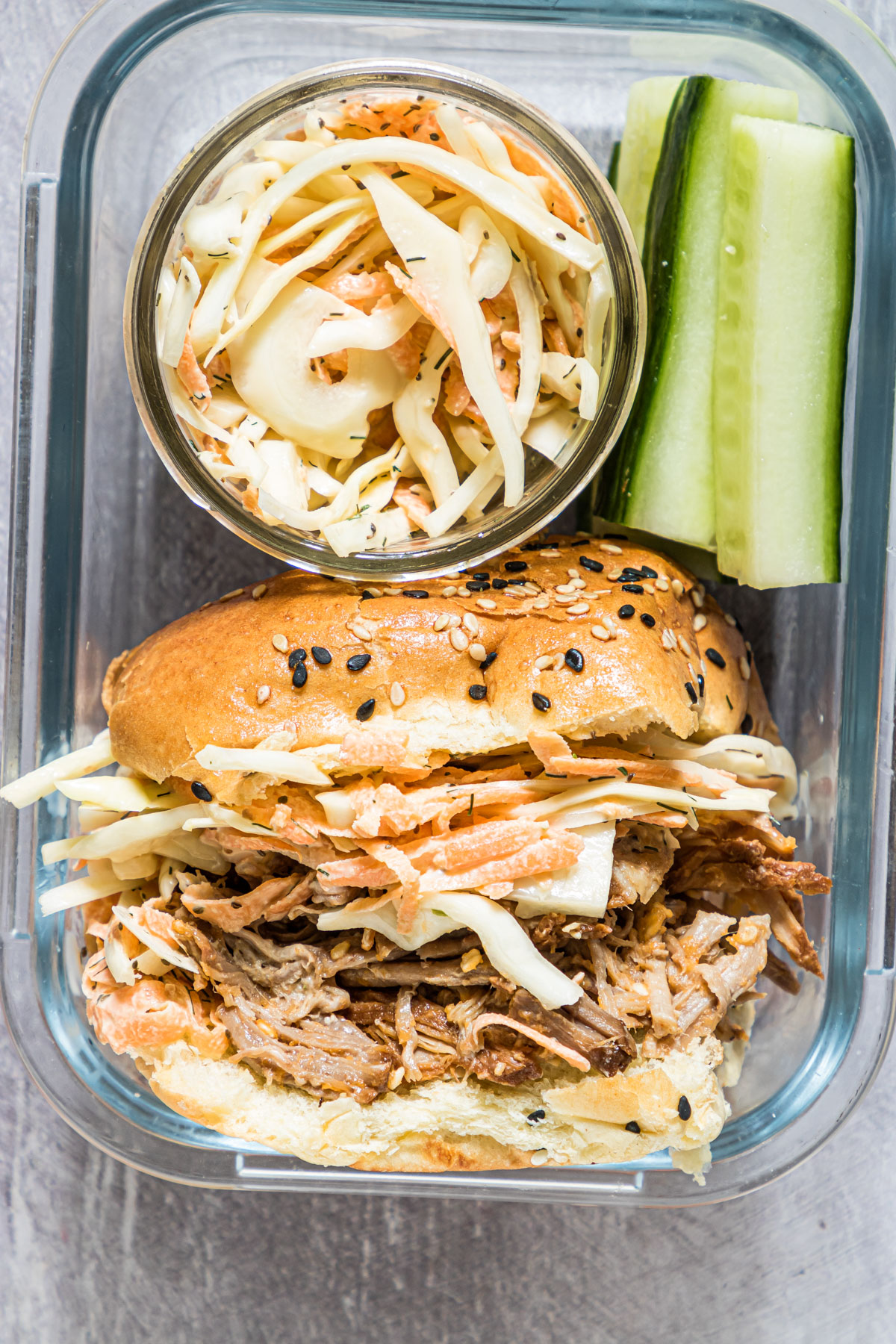 instant pot pulled pork packed in a glass meal prep container with coleslaw and cucumbers