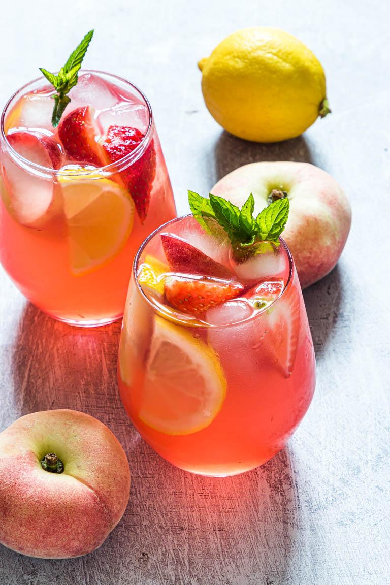 two glasses of the peach lemonade next to fresh peaches