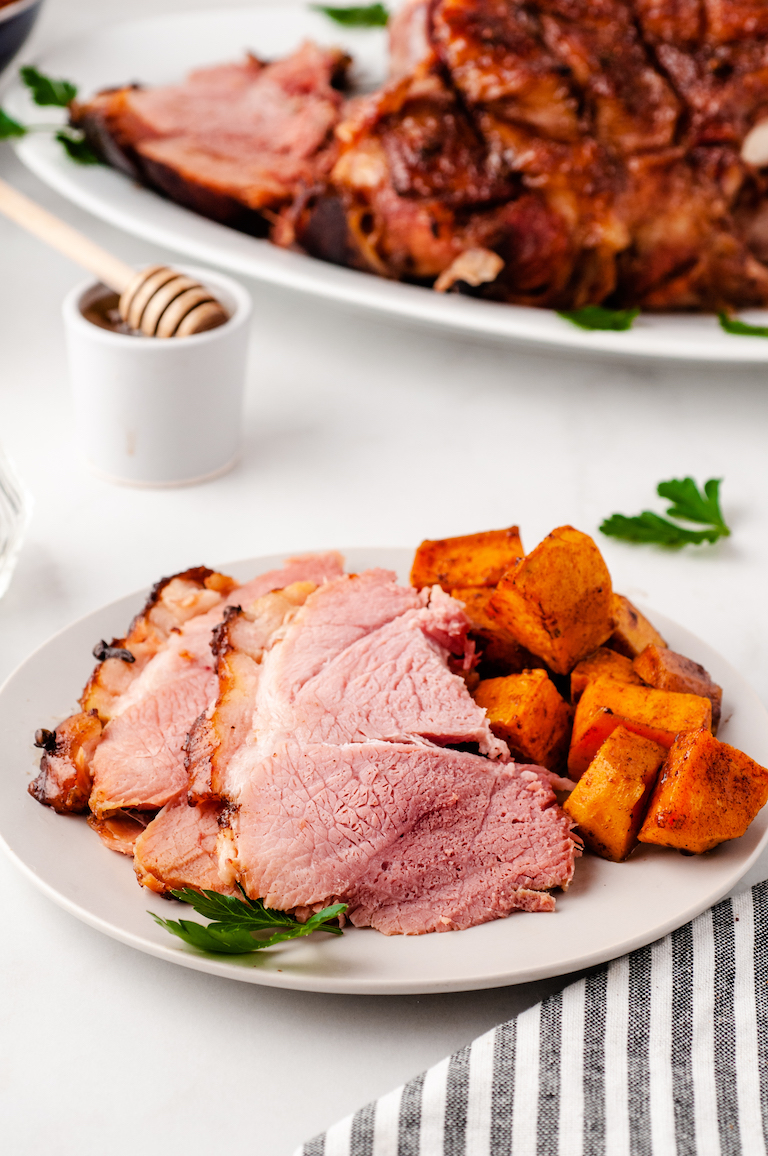 a dinner plate with slices of picnic ham and roasted sweet potatoes