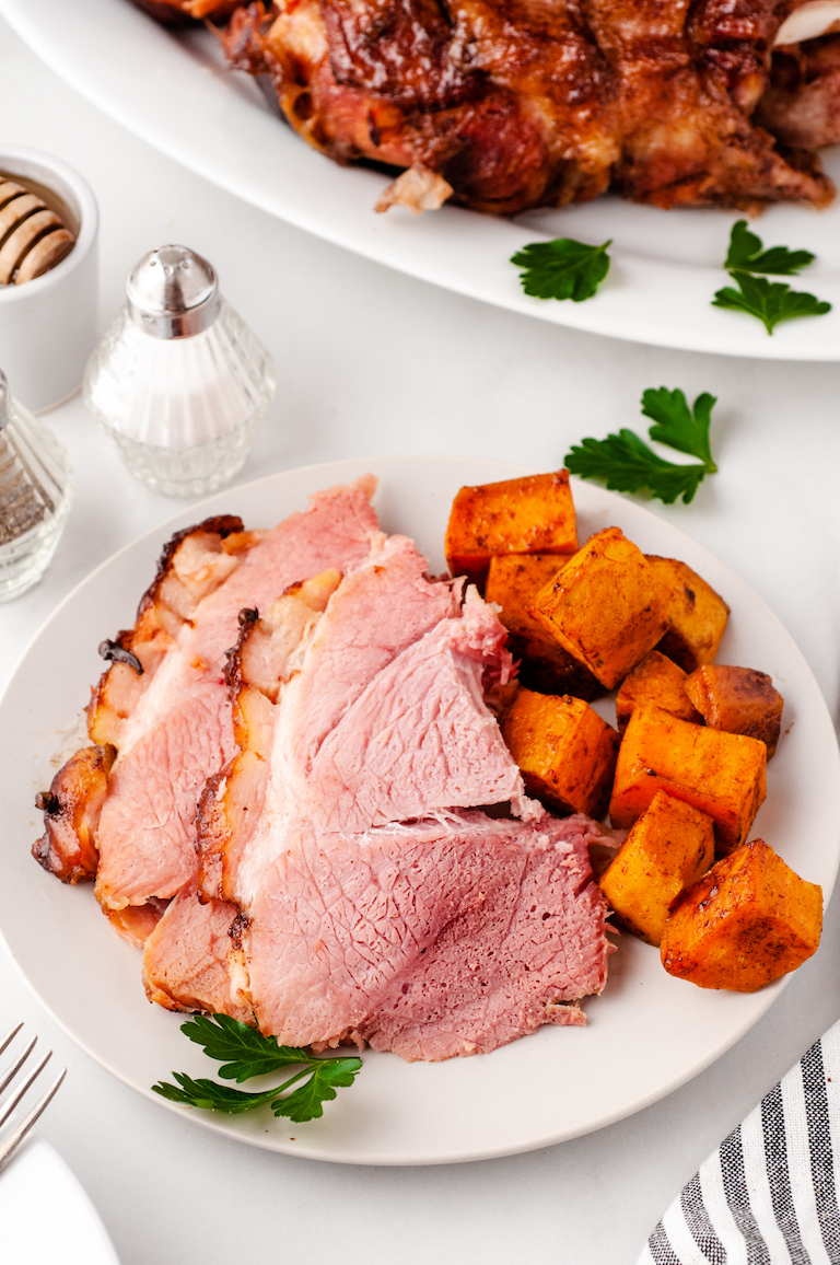 sliced picnic ham served with roasted sweet potatoes