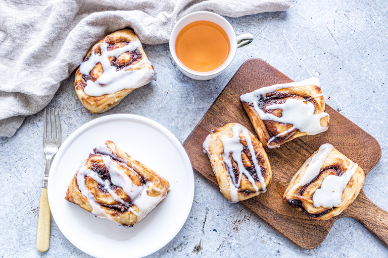 nutella pumpkin cinnamon rolls served with a cup of tea