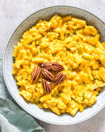 a bowl filled with instant pot pumpkin mac and cheese ands garnished with toasted pecans