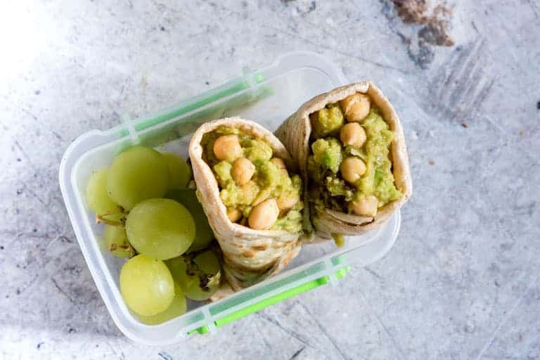 avocado wraps in a plastic container next to grapes