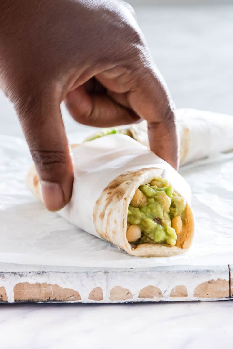 hand grabbing chickpea and avocado wraps placed on a board
