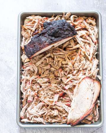 smoked pork shoulder being shredded on a baking sheet