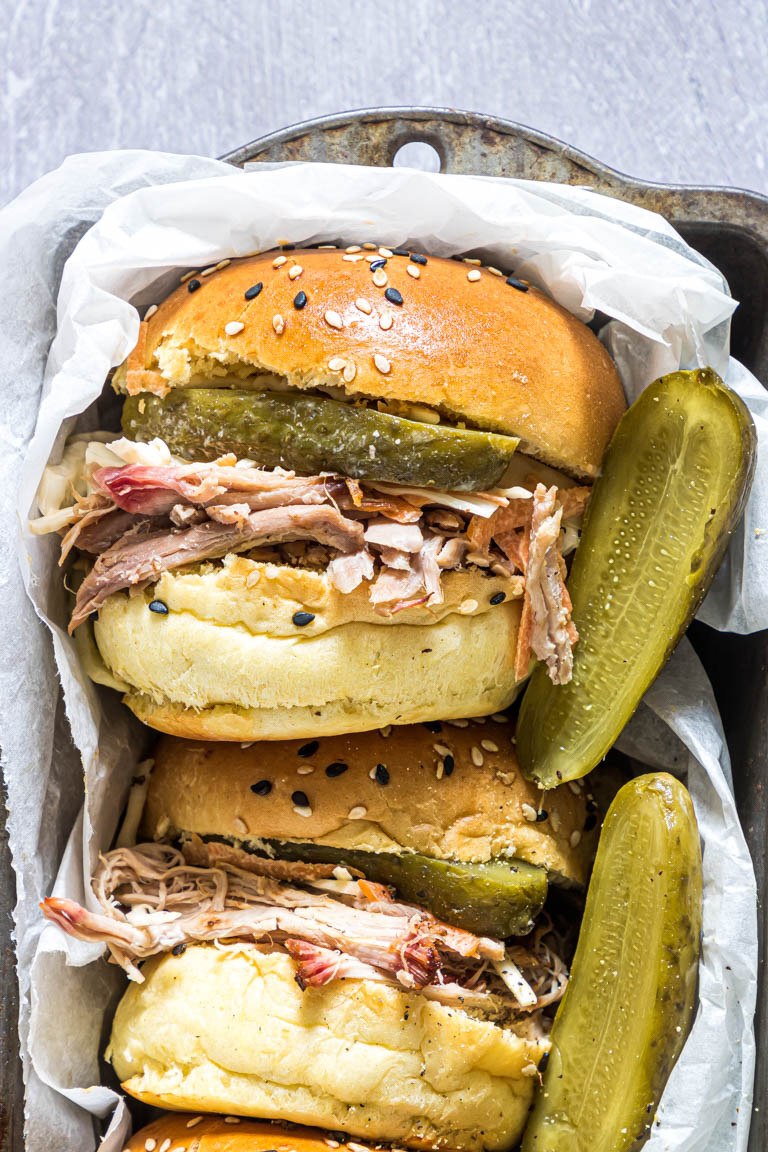 three smoked pork shoulder sandwiches served with pickles