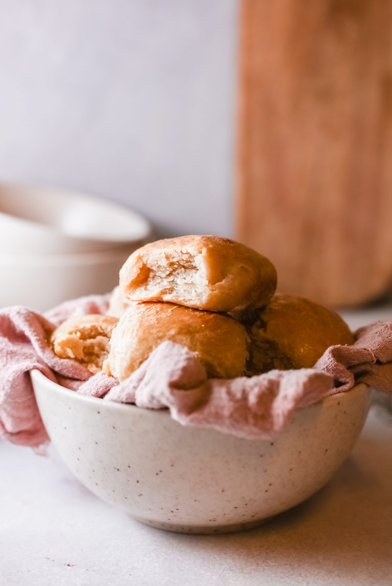 completed instant pot dinner rolls served in a bowl lined with a cloth towel