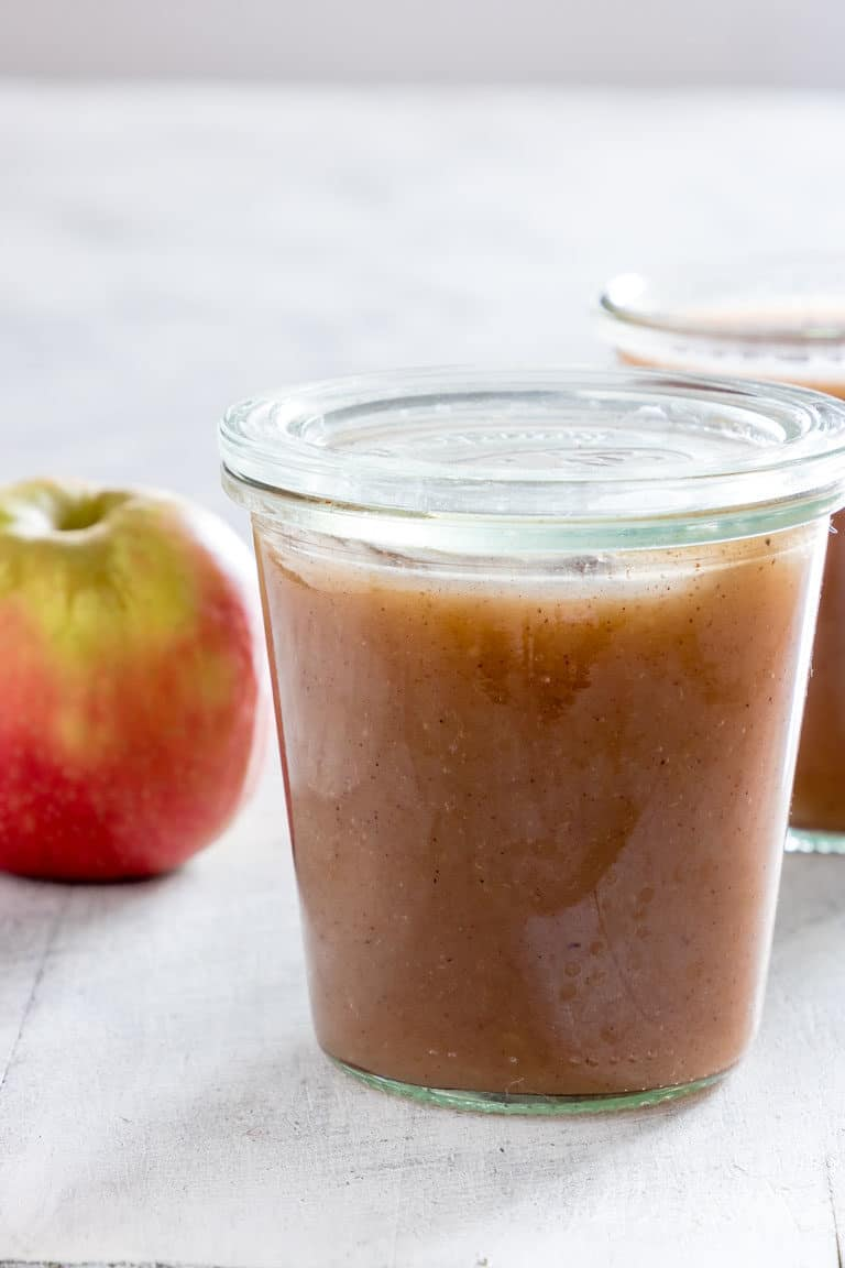A jar full of Instant Pot Applesauce with apple and another jar in the background