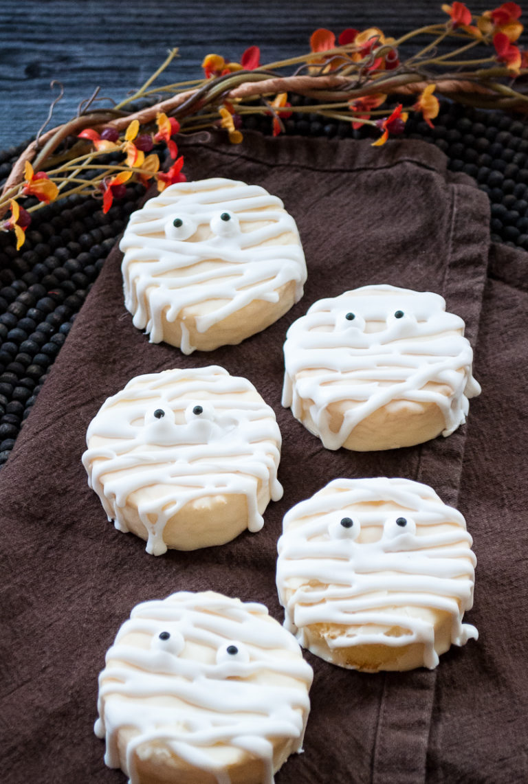 five of the finished mummy cookies on a dark brown cloth napkin