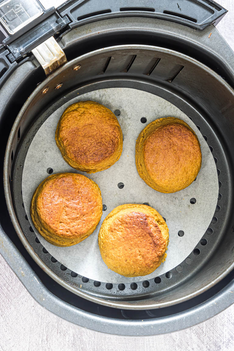 four cooked air fryer biscuits inside the air fryer basket