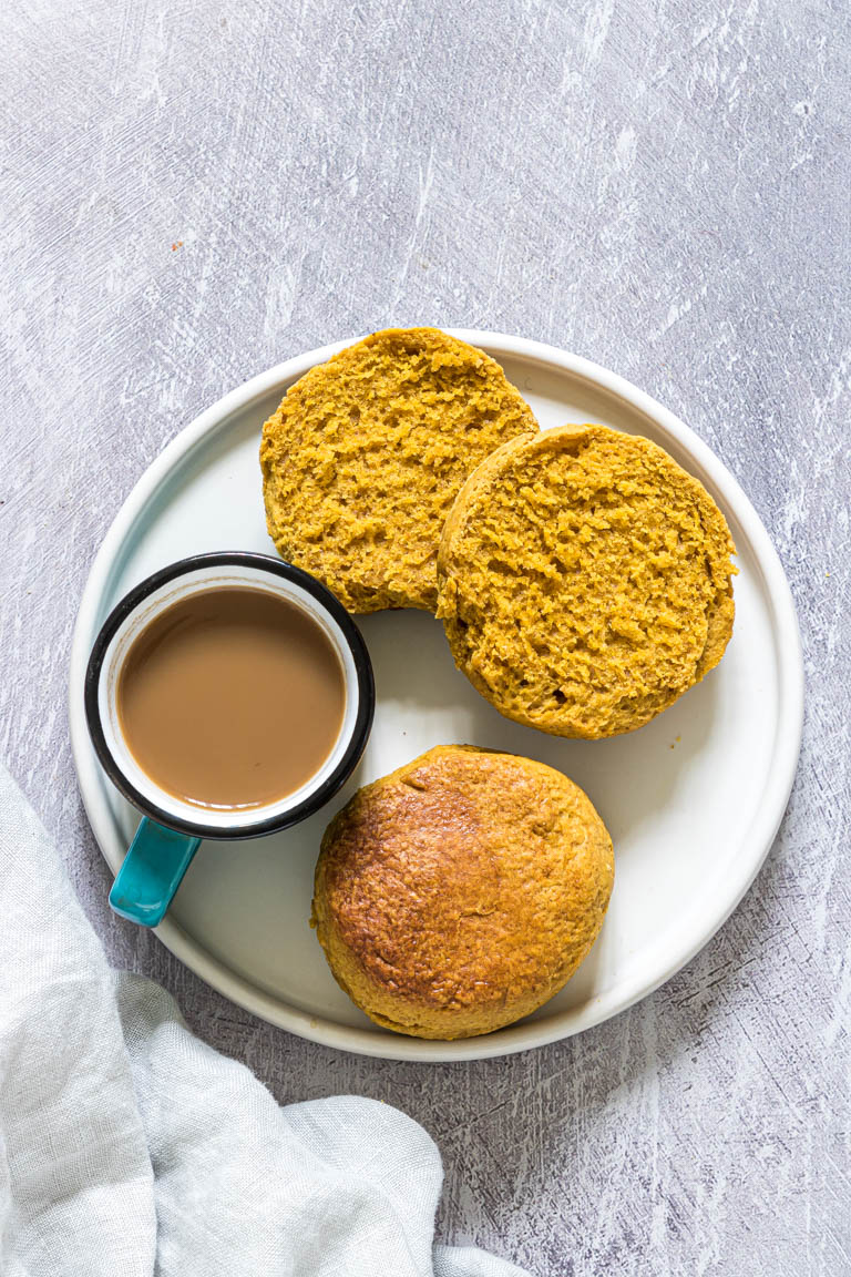 two pumpkin biscuits served on a white plate with a cup of coffee