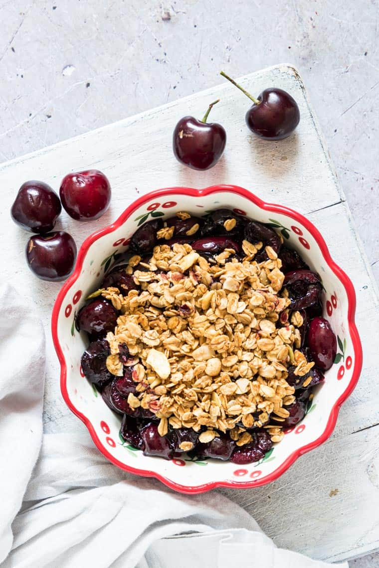a dish of air fryer cherry crisp with spoon, napkin and fresh cherries