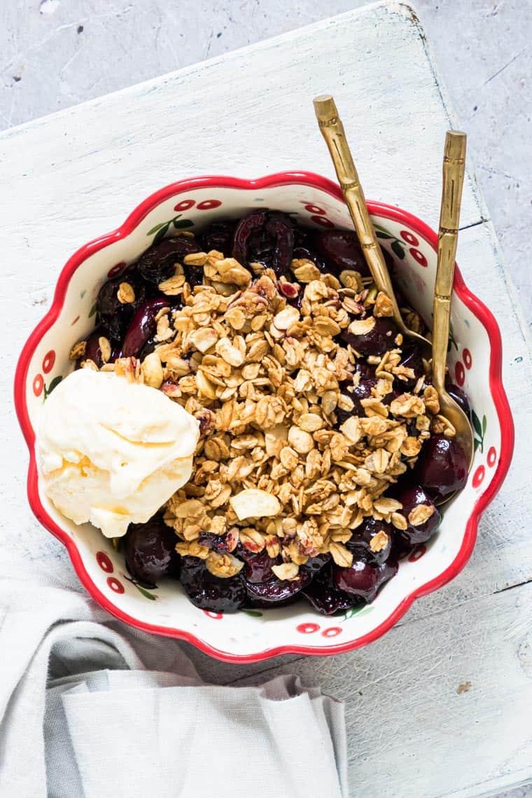 air fryer cherry crisp served with a scoop of vegan ice cream