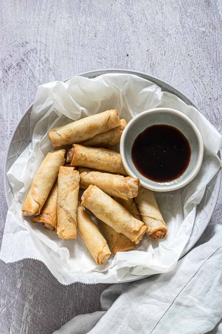 the completed air fryer egg rolls served on a platter lined with parchment paper