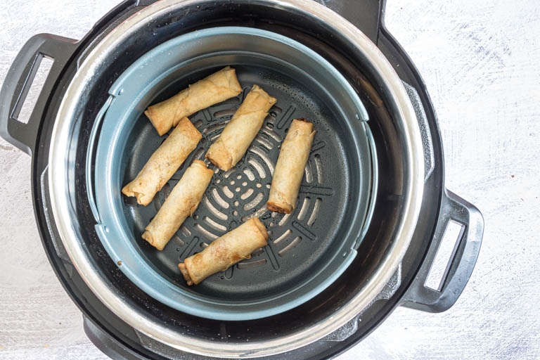 cooked air fryer egg rolls inside the instant pot air fryer insert