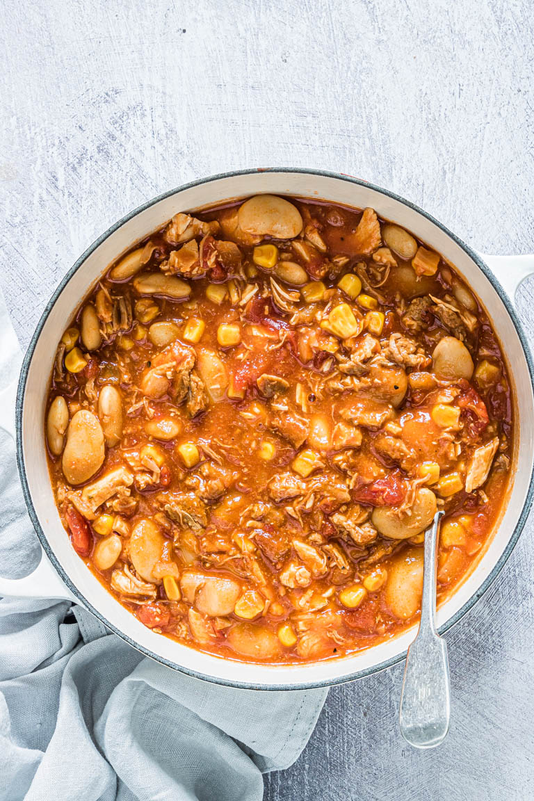 top down view of the completed brunswick stew served in a bowl with a spoon and cloth napkin