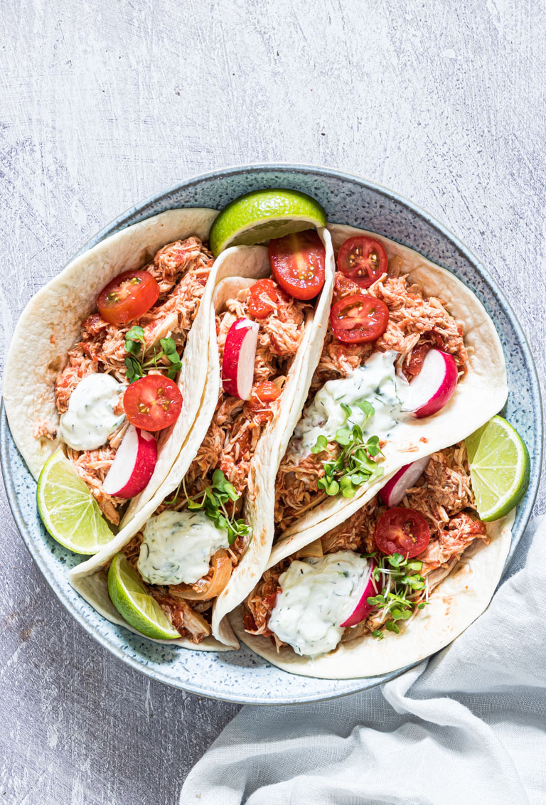 crockpot chicken fajitas served in tortillas with radishes and lime wedges