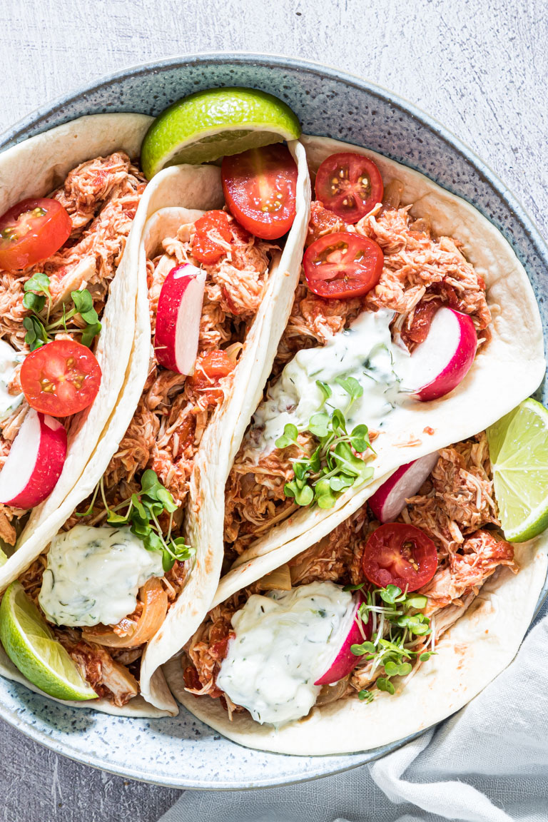 close up view of the finished crockpot chicken fajitas served in tortillas