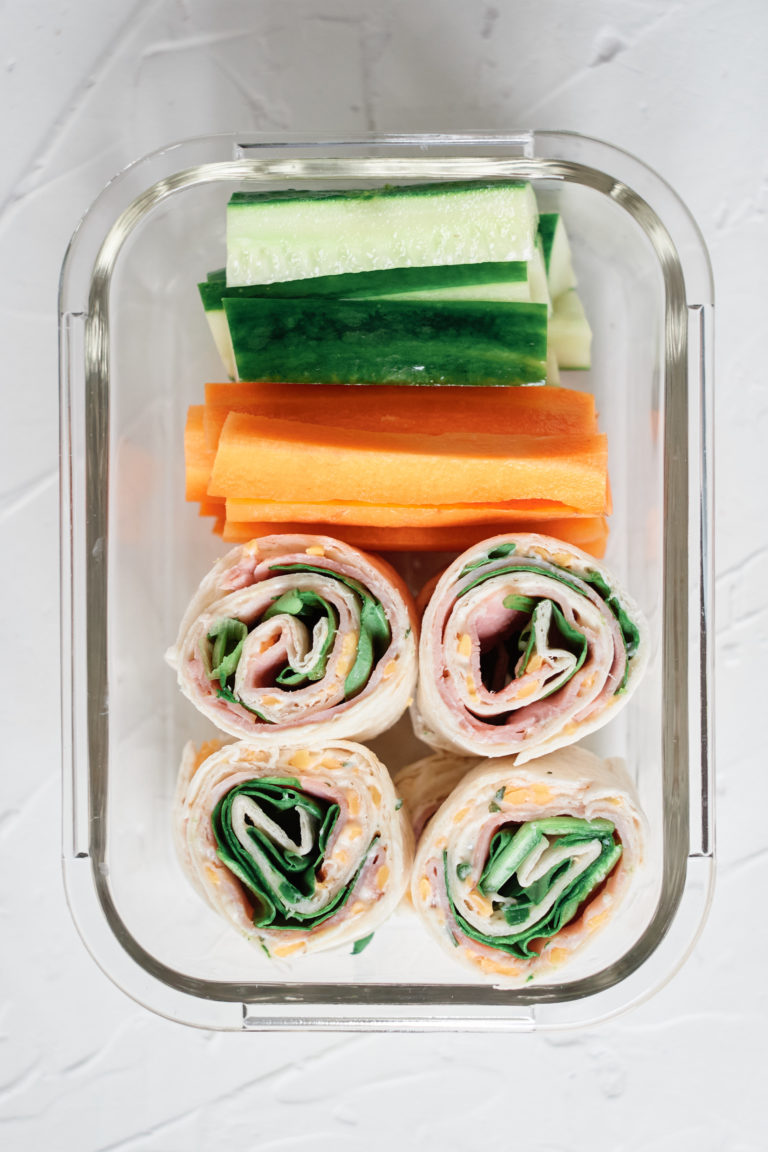 top down view of meal prep container packed with ham roll ups carrot and cucumber sticks