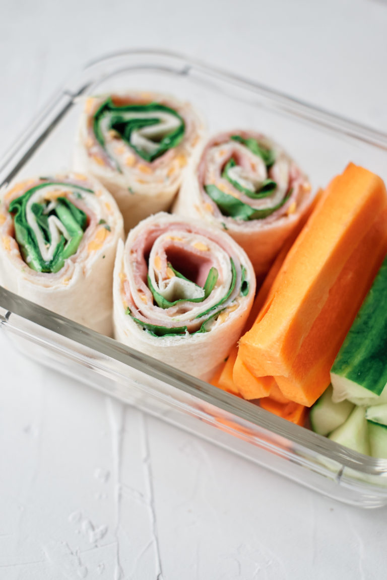 glass meal prep container filled with ham roll ups and veggie sticks