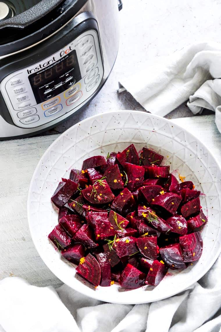 instant pot beets salad in a white ceramic bowl placed in front of the instant pot