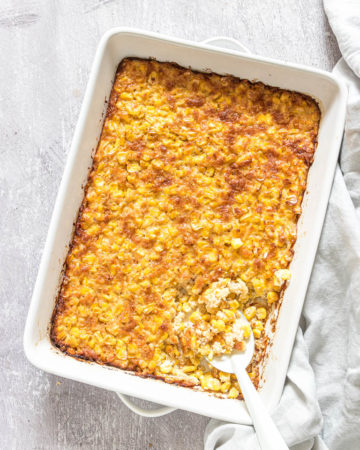 the cooked scalloped corn casserole inside a baking dish with a spoon removing a portion