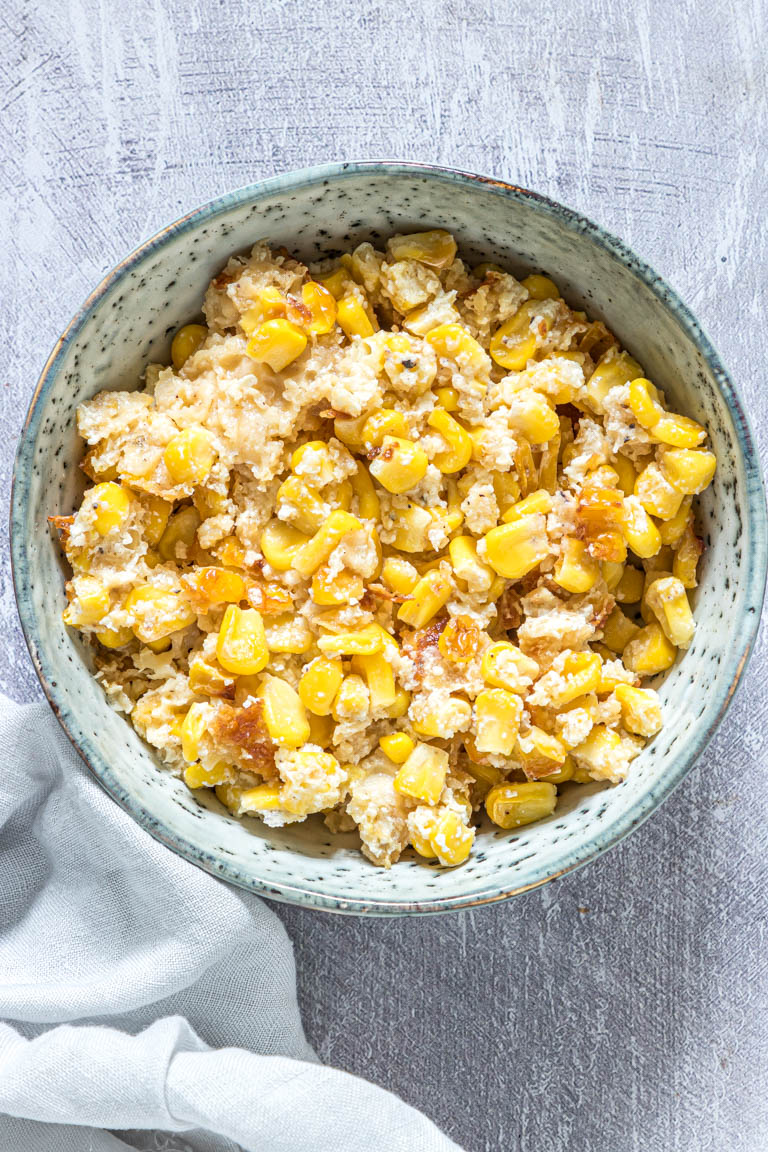 the finished scalloped corn served on a blue ceramic bowl with a cloth napkin