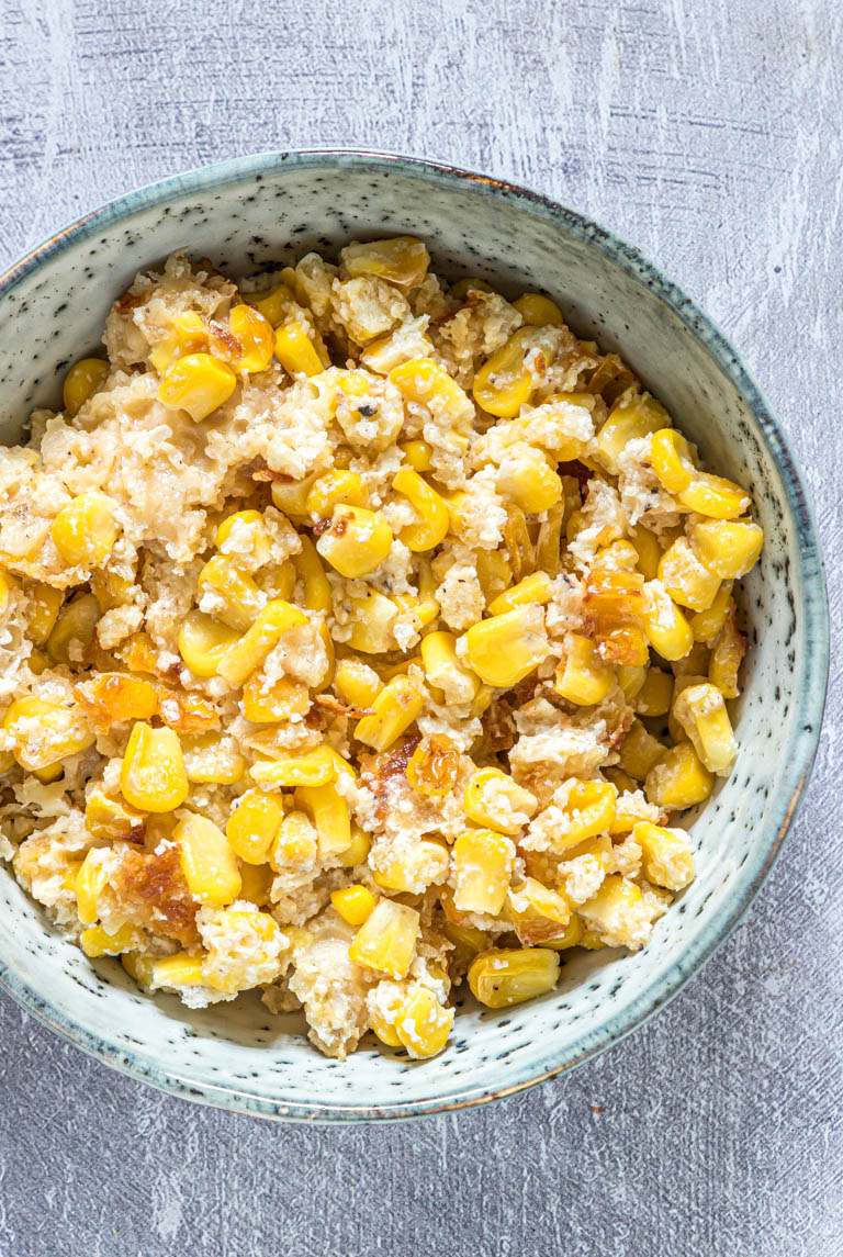 a blue bowl filled with scalloped corn casserole