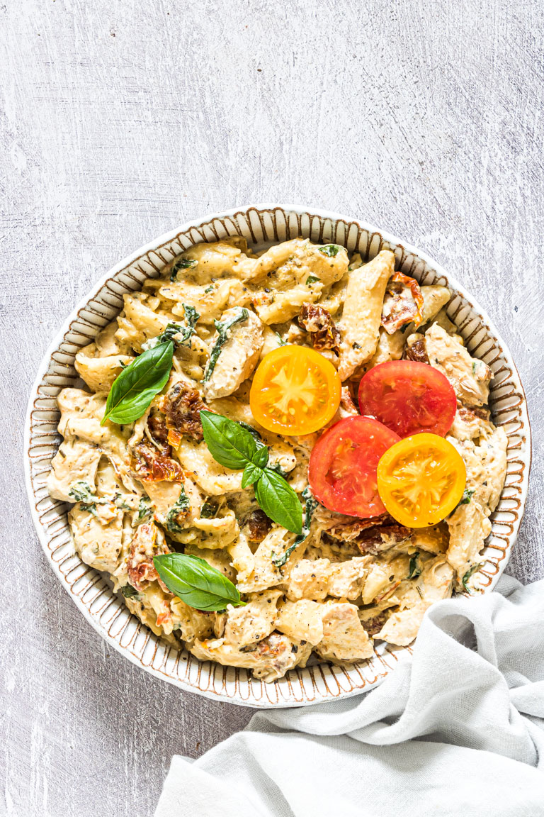 slow cooker pasta tuscan chicken pasta garnished with cherry tomatoes and served in a white bowl