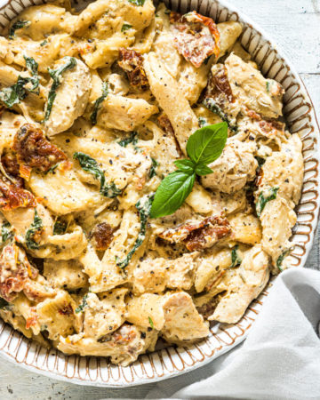 a bowl of slow cooker pasta tuscan chicken garnished with fresh basil and served with a cloth napkin