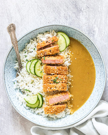 the completed SPAM Fritters Katsu Curry Recipe served in a bowl with rice and cucumber slices