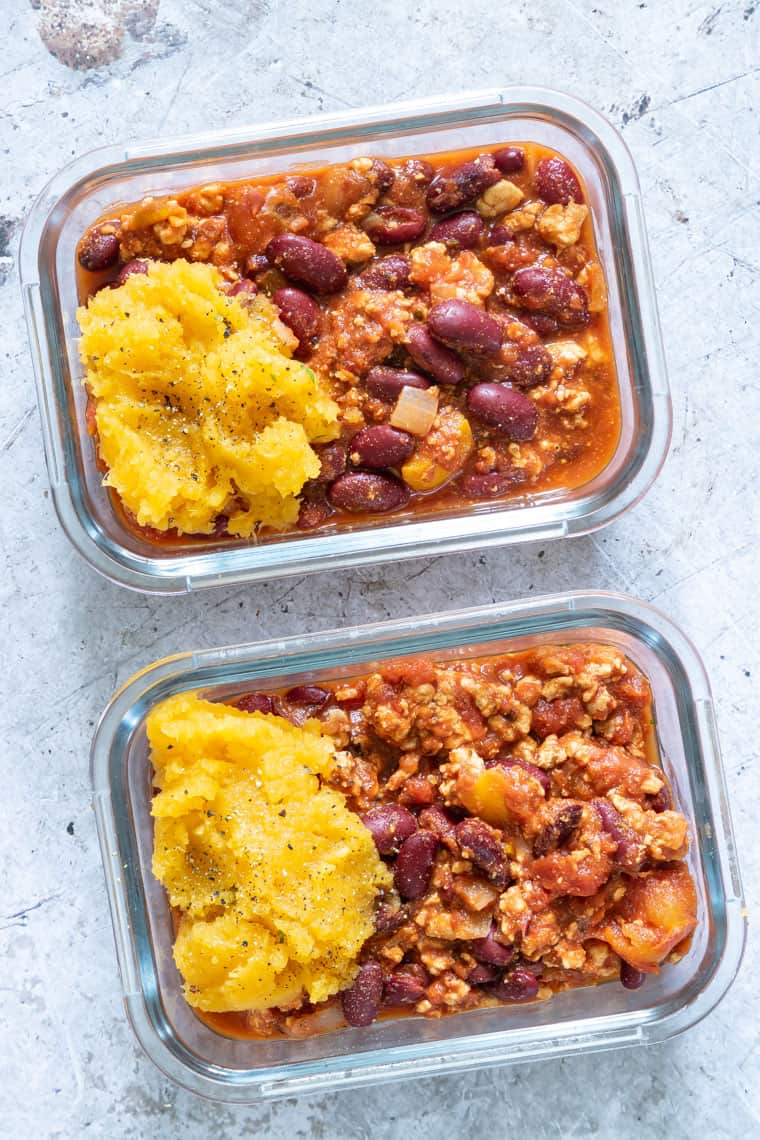 two glass meal prep containers filled with weight watchers turkey chili and a scoop of mashed sweet potatoes