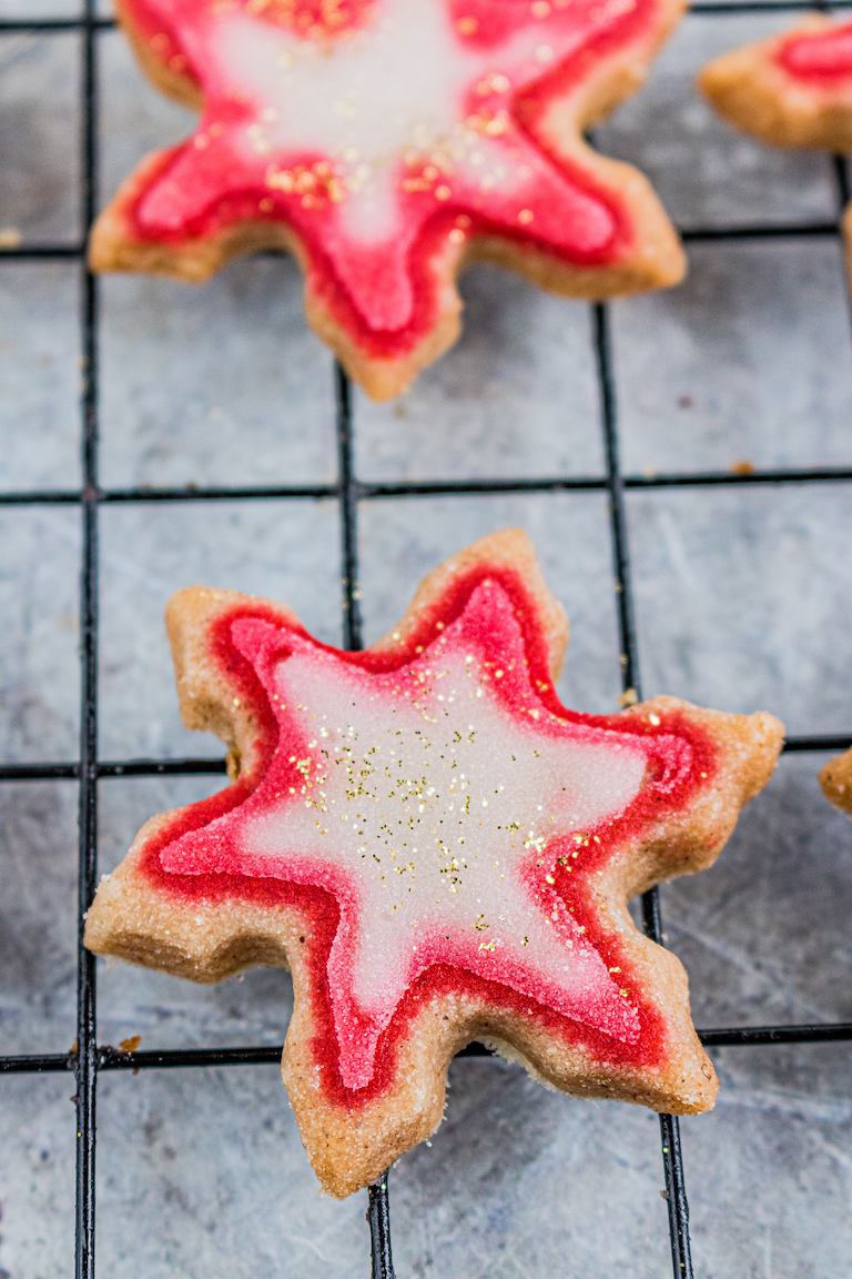 one of the finished decorated shortbread cookies on a cooling rack