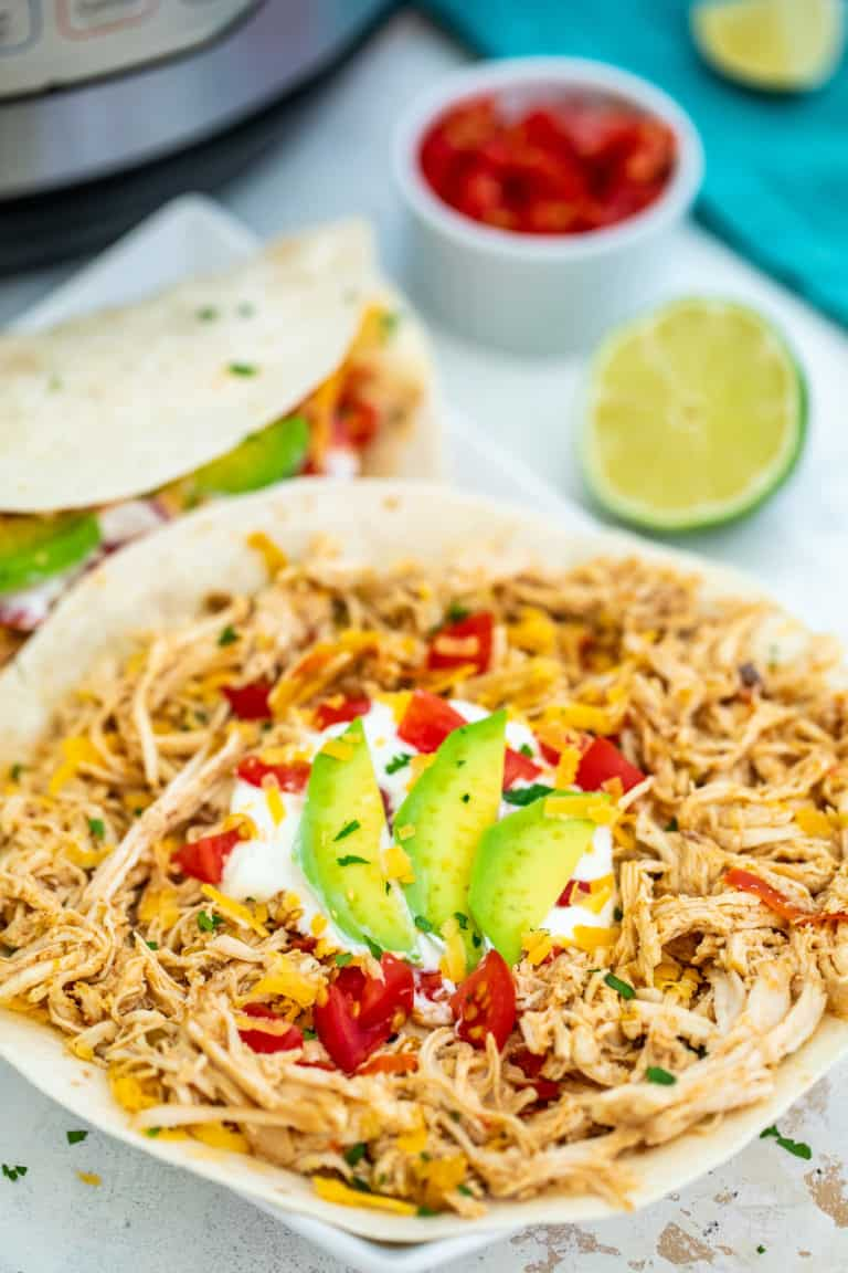 one assembled pressure cooker chicken fajita with lime and salsa on a wrap