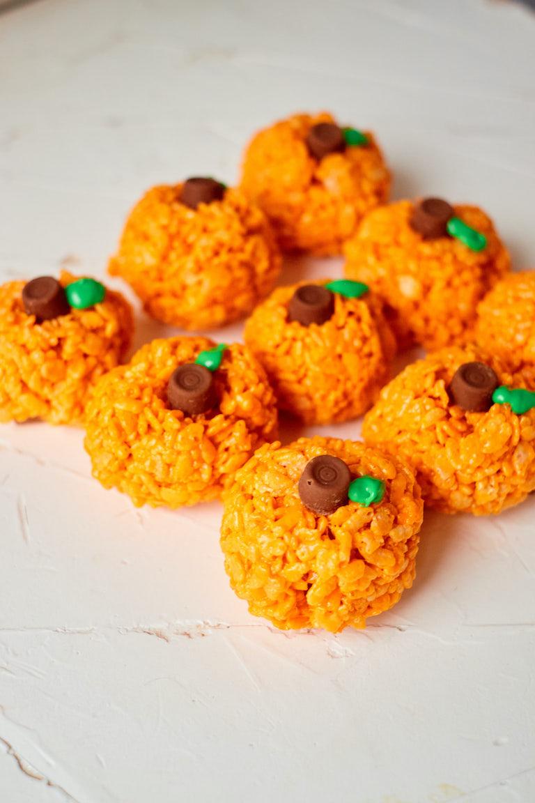 9 halloween rice krispie treats set up on a white countertop