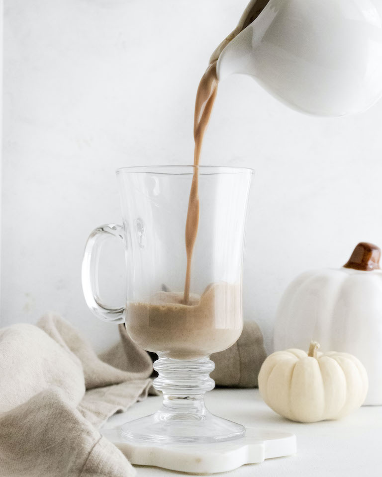 pumpkin spice dalgona coffee being poured into a glass