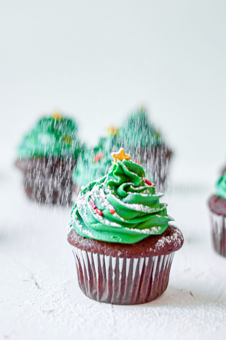 close up view of the finished Christmas tree cupcakes being sprinkled with powdered