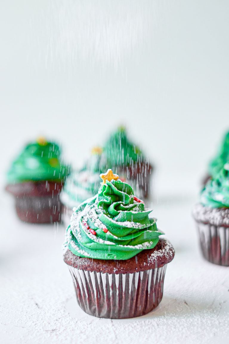 one christmas cupcake being dusted with powdered sugar