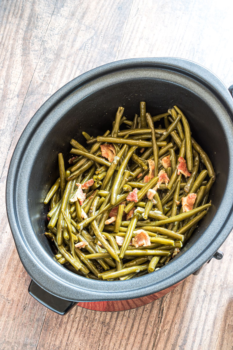 the cooked green beans and bacon inside the slow cooker