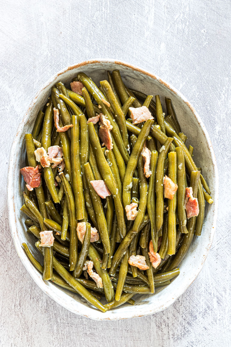 top down view of the finished green bean side dish served in a white bowl