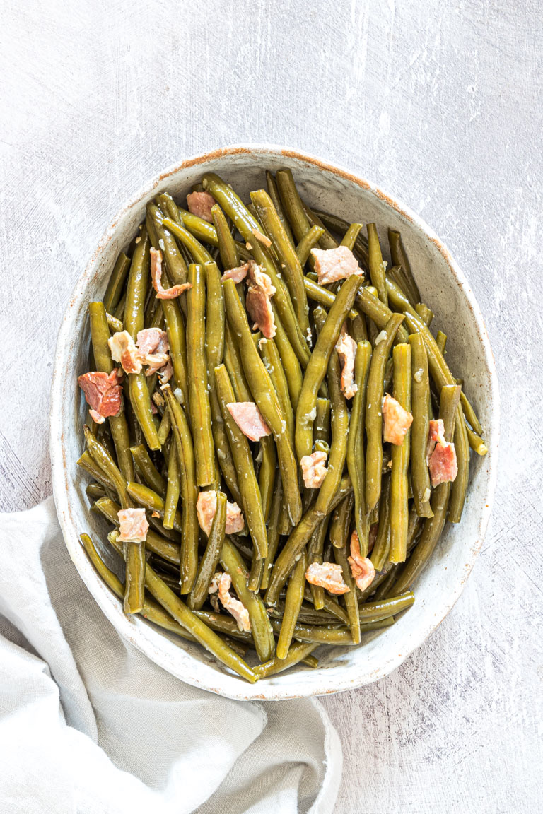 the completed crockpot green beans recipe served in a white dish