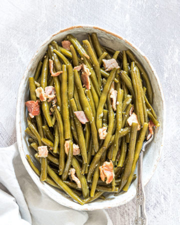 the finished crockpot green beans served in a white dish with a silver spoon