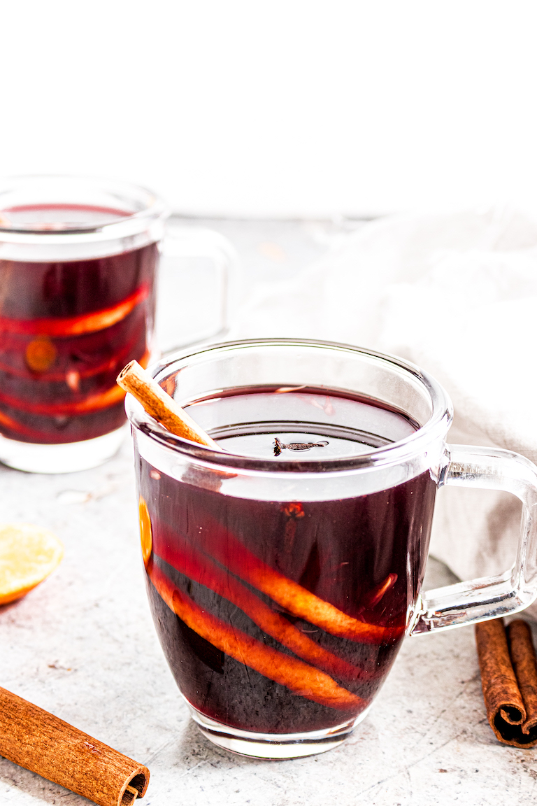 two mugs of mulled wine garnished with cinnamon sticks